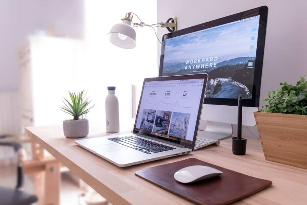 MacBook Pro on table beside white iMac and Magic Mouse