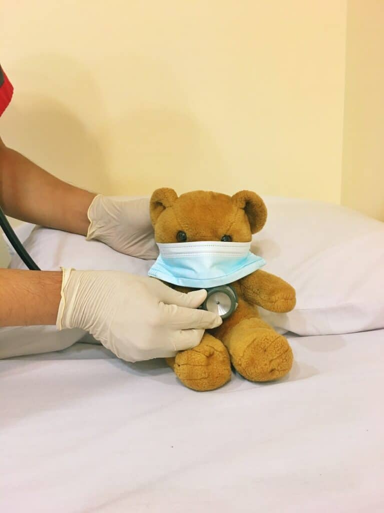 brown bear plush toy on white bed